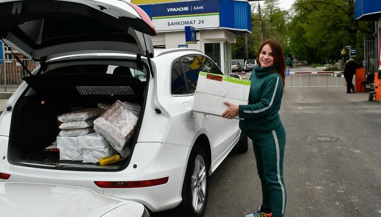 Багажник девушки забит продуктами и подарками для пенсионеров и многодетных семей