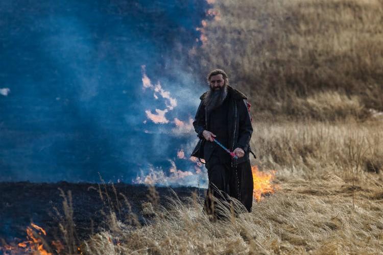 Пал травы не страшен для священника. Фото: Агата КАРАСЕВА.