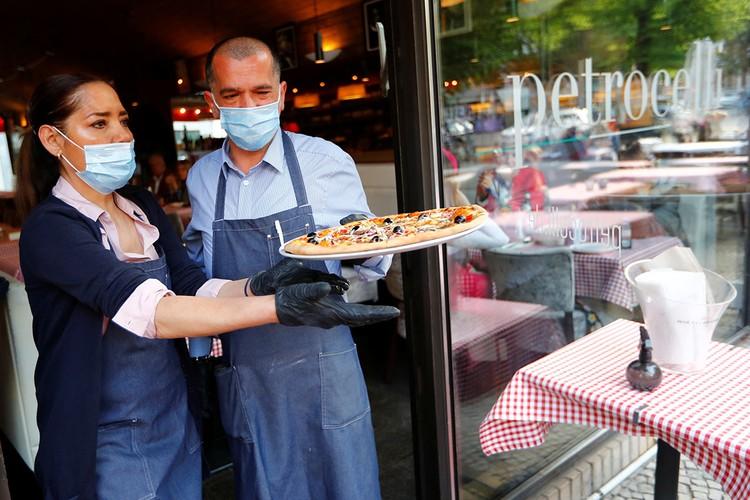 Работа официантов в берлинском уличном кафе.
