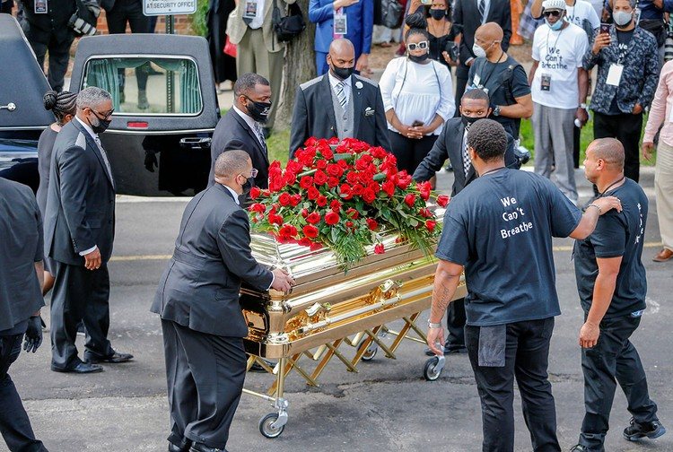 Позолоченный гроб Джорджа Флойда загружают в катафалк.