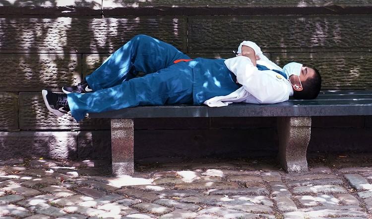 Медработник отдыхает на скамейке после смены, Нью-Йорк.