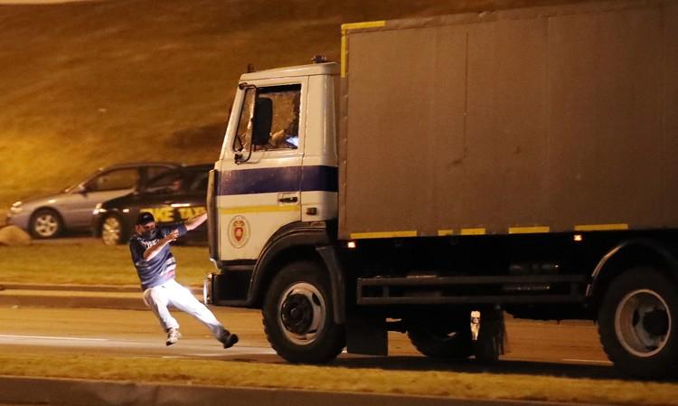 Полицейский автозак сбивает участника акции протеста, пытавшегося его остановить. Фото: ЕРА/ТАСС