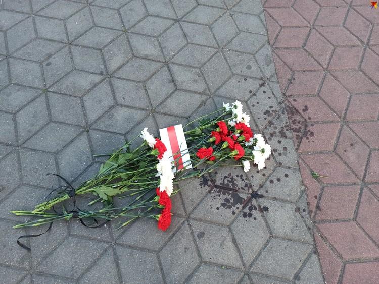 Кровь пострадавшего от резиновой пули и цветы в центре Советской.