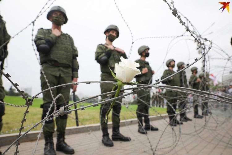 Армейцам, которые стояли на страже стелы, люди оставляли цветы прямо в колючей проволоке.