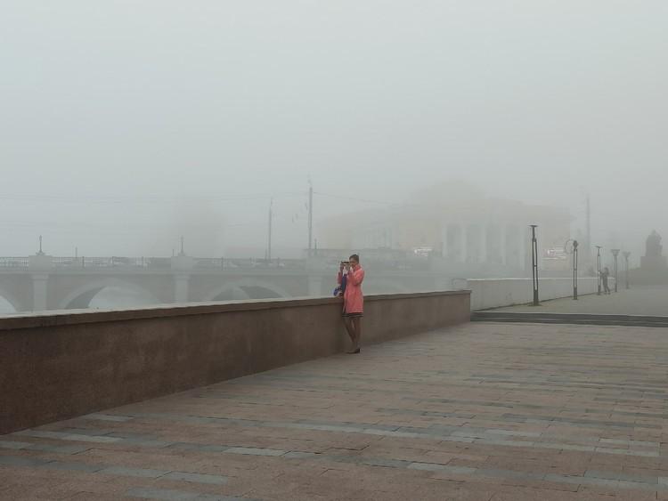 Люди останавливаются, чтобы сфотографировать туман