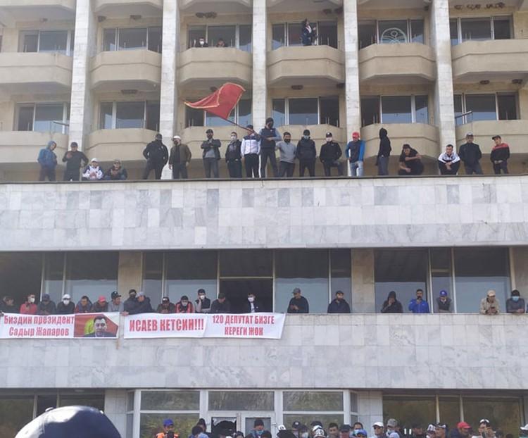 Надписи на плакатах, вывешенных митингующими на здании гостиницы, гласят: «Наш президент - Садыр Жапаров», «Исаев, уходи!» (спикер парламента - Прим. ред.), «Нам не нужны 120 депутатов».