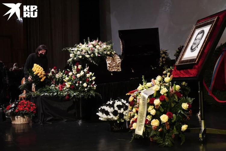 Около установленного на сцене гроб стоит много букетов цветов