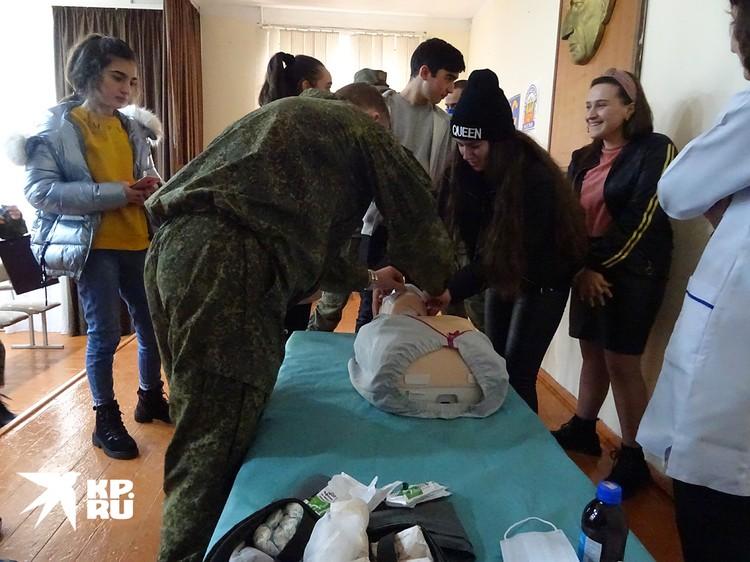 После «урока миротворца» девочки окружают манекен, на котором учатся делать искусственное дыхание и массаж сердца