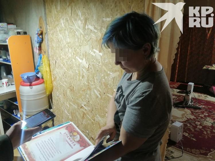 Женщина показывает фотоальбом и дипломы сына.