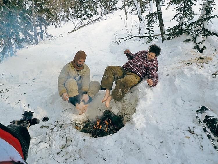Сцена под кедром. Наши актеры пытаются согреть надкостром замерзшие ноги. Так, по нашим предположениям, могли отогреваться дятловцы, укрывшись в лесу после панического бегства изпалатки.