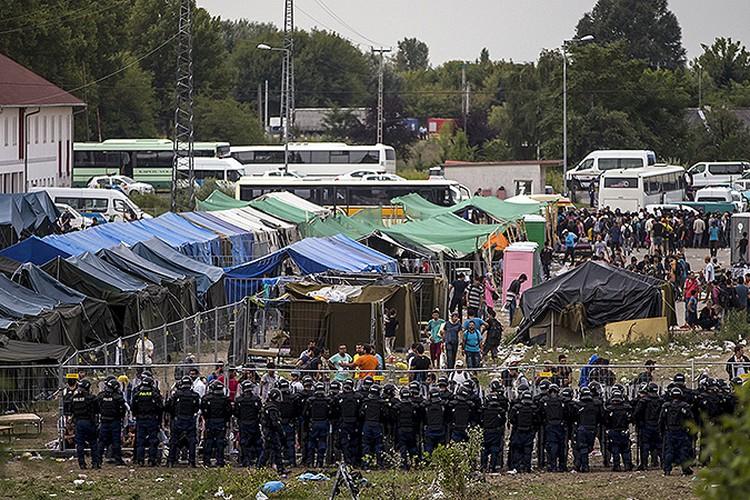 Лагерь беженцев в Венгрии плотно окружен охраной.